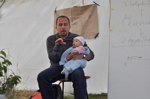 Takács-Sánta András kislányával a karján tart előadást a közösségek kialakításának fontos lépéseiről